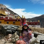 """Angela was sitting in front of the Ganden Monastery, saying """"hello"""" to everyone."""