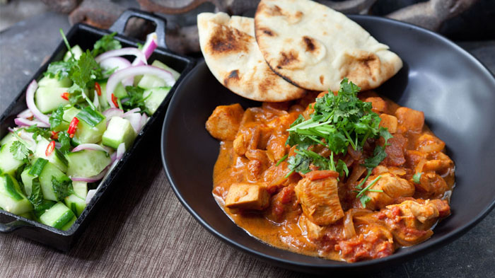 Chicken tikka masala with minted cucumber salad and naan bread