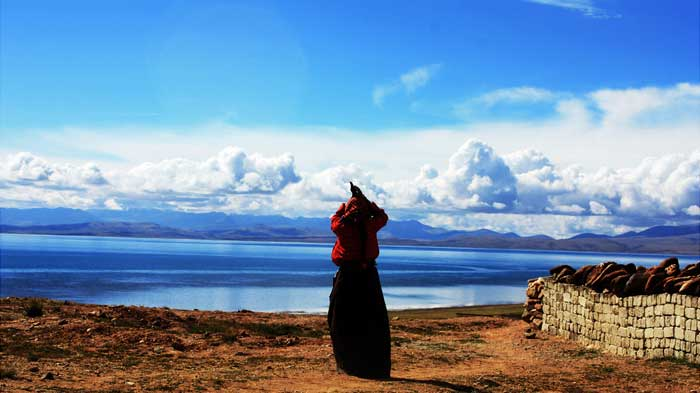 A Tibetan pilgrim is praying at the lake side.