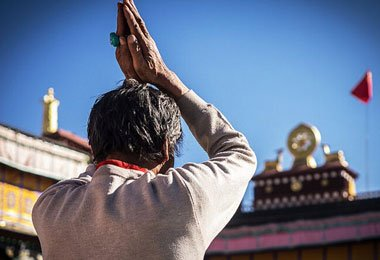 A Tibetan pilgrim is worshipping  Jokhang Temple